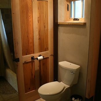 Sliding barn door separating half bath from shower