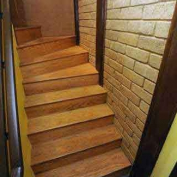 Site-made compressed earth block walls in the stairwell. The downstairs can function as a separate apartment or business.